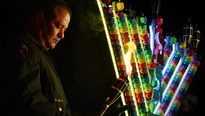 John Reilly, captain of the Ventura County Sheriff's Department in Moorpark, holds the torch to light the menorah made of dreidels during a Hanukkah festival two years ago.