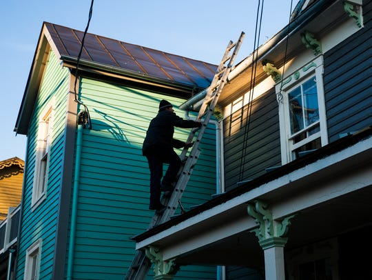 John Panzino Sr., of L&L Roofing, climbs up to the