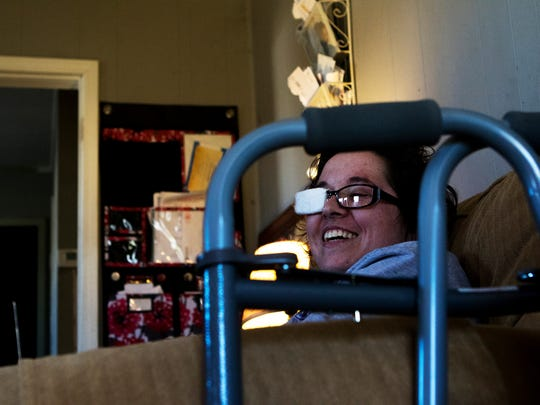 Cody Goodrich sits in an armchair in the living room of the home she and her mother rent in West Monroe on Wednesday, February 15, 2017. The paper towel wrapped around the right lens of her glasses is meant to help cure double vision, which was caused by the injury she sustained when an ex-boyfriend shot her in the head. She uses a walker and wheelchair to get around and is re-learning to walk, talk and read. Still, she constantly laughs and jokes with her mother. She joked that the two of them could be a comedy act.