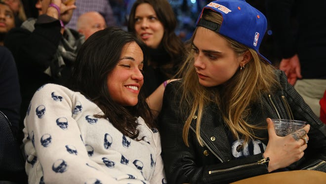 Michelle Rodriguez sits with with model Cara Delevingne during the game between the New York Knicks and the Detroit Pistons at  Madison Square Garden on Jan. 7 in New York City.