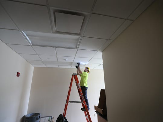 Dan'l Jackson of Greece, a third year electrician apprentice, working with Shuler-Hass Electric, works on replacing light fixtures  at Roberts Wesleyan College in Chili Monday, June 8, 2015.