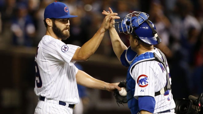 Chicago Cubs starting pitcher Jake Arrieta, left, and catcher Miguel Montero high five.