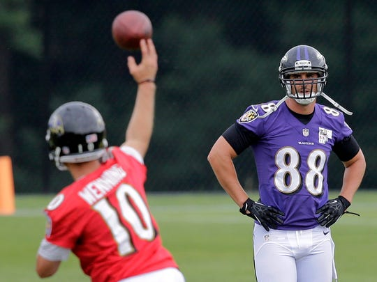 Baltimore Ravens tight end Dennis Pitta, right, walks past quarterback Keith Wenning as he throws a pass during NFL football minicamp, June 19, 2014, at the team's practice facility in Owings Mills, Md.