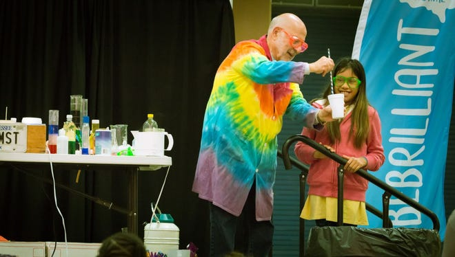 Al Hazari, retired professor in the University of Tennessee's chemistry department, demonstrates a science project with a student at the Tennessee STEAM Festival Oct. 17, 2017.