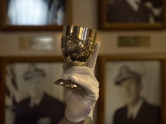 A Battleship New Jersey volunteer holds a cup from