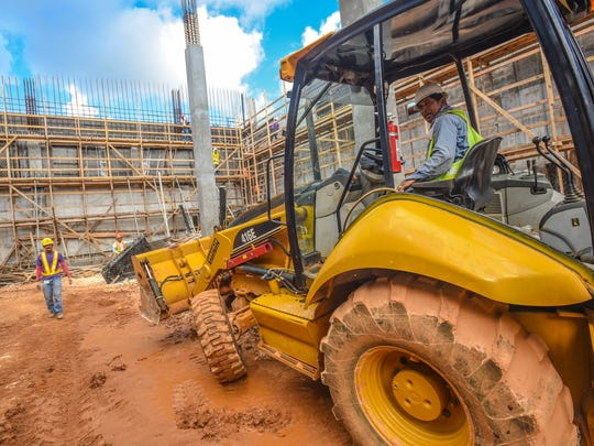 In this file photo, 5M Construction Corporation employees work at a warehouse building project in Tamuning. 5M is one of several companies suing the federal government for rejecting visa applications for foreign workers.