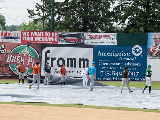 Northwood League All-Star players help pull the tarp