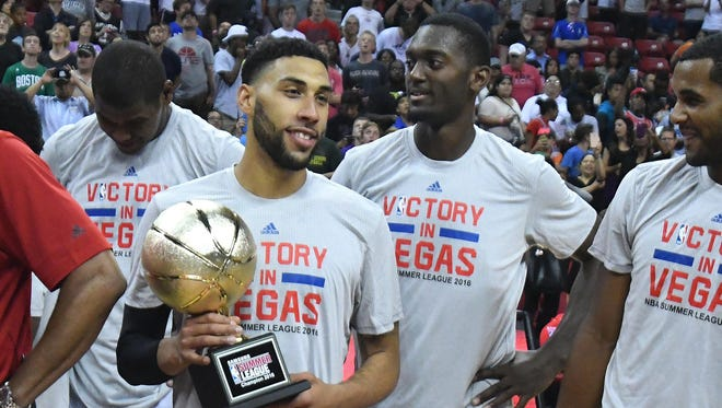 Denzel Valentine, selected No. 14 overall by the Chicago Bulls in the 2016 NBA draft, holds the championship trophy after leading Chicago to a 7-0 mark in summer-league play.