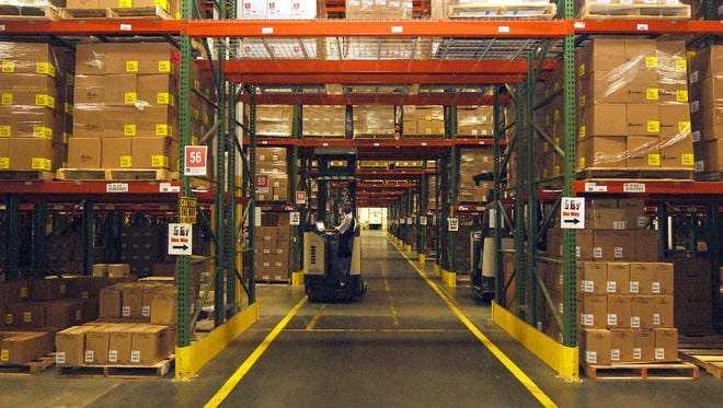 Meridian -- A worker removes packaged goods in a newer warehouse at the Meridian Avery Dennison plant.