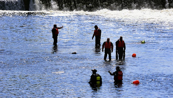 Divers fan out to search the shallows of the Grand River near the Brenke Fish Ladder Friday after a fisherman discovered the lower part of a human leg attached to a tennis shoe while fishing.