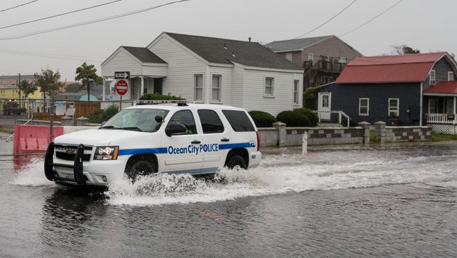 A Ocean City Police Department vehicle makes it's way through the flood area along St. Louis Avenue near 2nd Street in Ocean City Thursday afternoon.