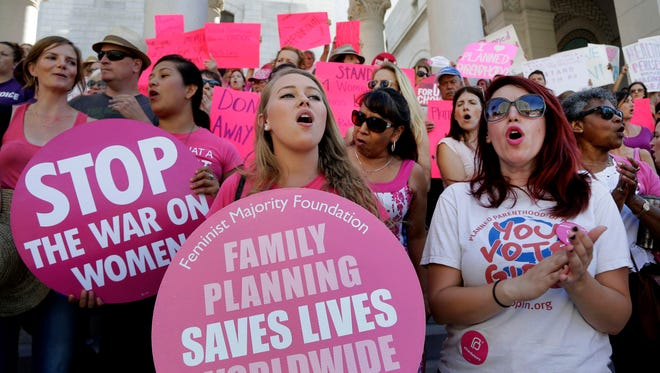 """In this Sept. 9, 2015 file photo, Planned Parenthood supporters rally for women's access to reproductive health care on """"National Pink Out Day'' at Los Angeles City Hall."""