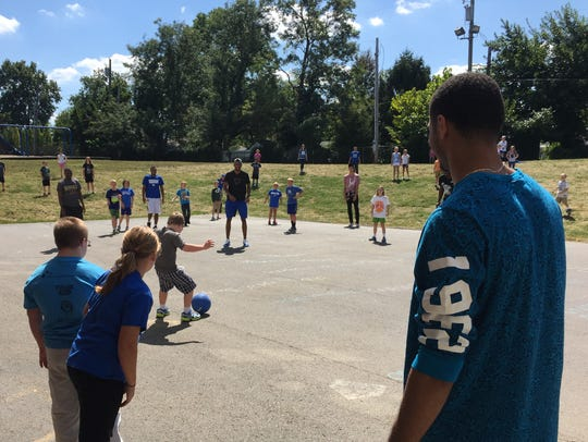 UK's Jamal Murray looks on as children play kickball.