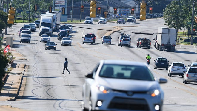 A pedestrian crosses White Horse Rd. in Greenville on Tuesday, May 16, 2017.