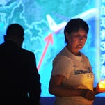 A Chinese relative (R) of passengers on the missing Malaysia Airlines flight MH370 holds a candle as she takes part in a prayer service at the Metro Park Hotel in Beijing on April 8, 2014. The hunt for physical evidence that the Malaysia Airlines jet crashed in the Indian Ocean more than three weeks ago has turned up nothing, despite a massive operation involving seven countries and repeated sightings of suspected debris. AFP PHOTO / WANG ZHAO        (Photo credit should read WANG ZHAO/AFP/Getty Images)