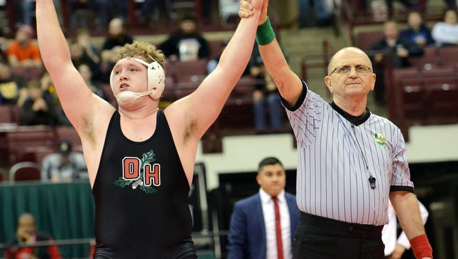 A referee raises the arm of Oak Harbor's Brandon Garber after Garber won the Division III 285-pound state wrestling title Saturday in Columbus.