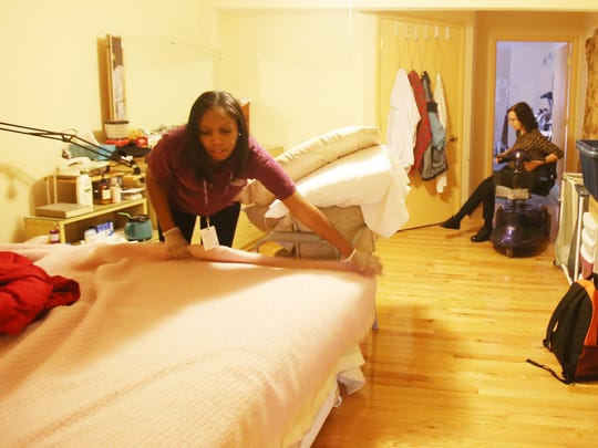 "Celeste Cayton, 24, of Detroit, left, is a caregiver for Home Instead Senior Care. She makes the bed of one of her clients, Elizabeth Kertesz-Hacket, at her Royal Oak home Wednesday, Oct. 29, 2014. Kertesz-Hacket says about her care by Cayton that she is ""wonderful"" and ""she's helped me a huge amount."""