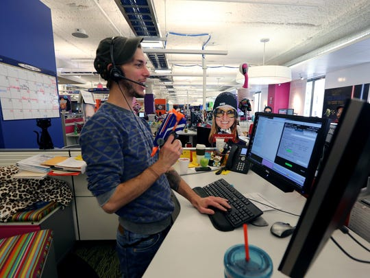 Benjamin Amiot, 32, a client care specialist at Quicken Loans, is ready for a nerd gun attack while he works with a client on a call on Oct. 10.