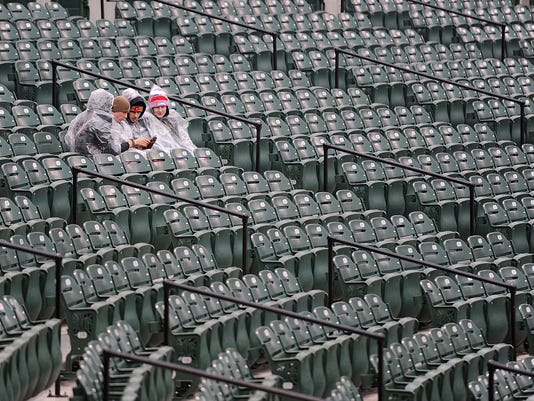 Fans sit wearing ponchos as they wait the start of the Baltimore Orioles and Tampa Bay Rays baseball game, Saturday, April 9, 2016 in Baltimore. (AP Photo/Gail Burton)