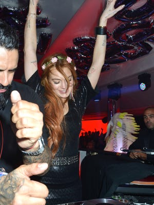 CANNES, FRANCE - MAY 21:  A DJ and Lindsay Lohan performs during the VIP Room JW Marriot : Day 8 - The 67th Annual Cannes Film Festival on May 21, 2014 in Cannes, France.  (Photo by Foc Kan/FilmMagic)