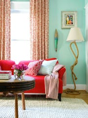 A den showcases a fresh, feminine drapery fabric by Tilton Fenwick and a less expected feminine color scheme of mint green and fire engine red.