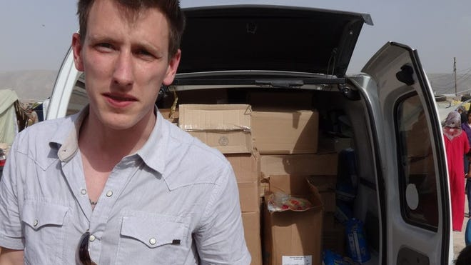 This undated photo provided by Kassig Family shows Peter Kassig standing in front of a truck filled with supplies for Syrian refugees. Confronted by terrorists beheading Americans, President Barack Obama has ordered a review of how the United States responds when citizens are taken hostage overseas.