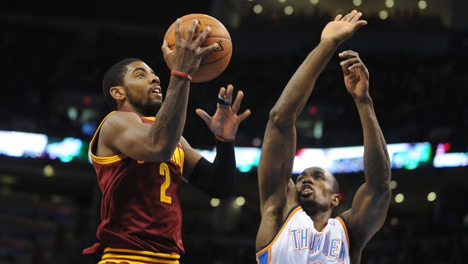 Cleveland Cavaliers point guard Kyrie Irving (2) attempts a shot against Oklahoma City Thunder power forward Serge Ibaka (9).