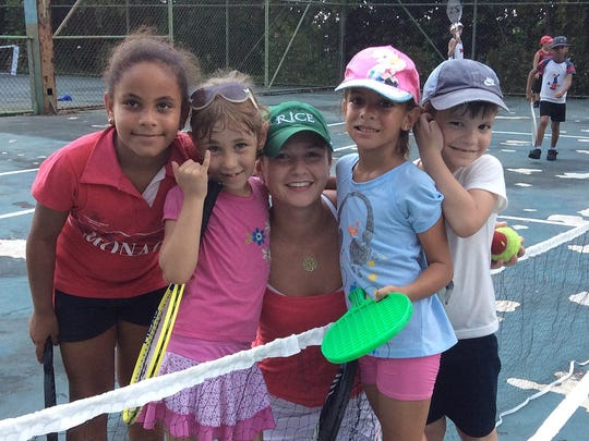 Sophia Lothrop of Rice Memorial High School went to Cuba with Kids on the Ball program. She is pictured with young Cuban players on a National Tennis Center court in October 2015.