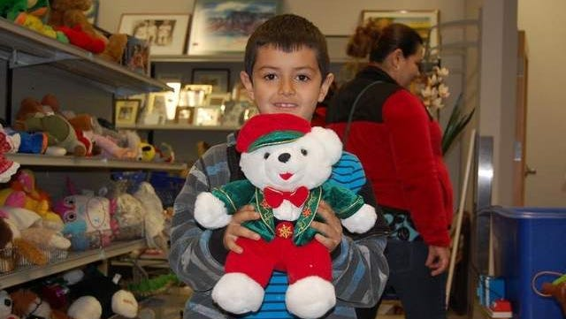 Joel Espinosa, 7, holds up his free stuffed animal Saturday at a Goodwill store in Colorado.