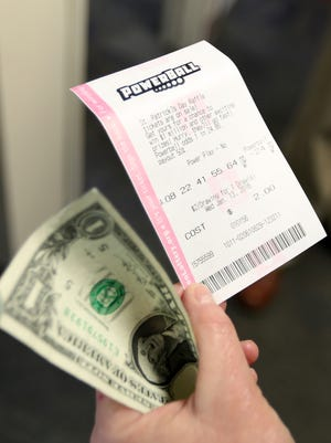 Statesman Journal columnist Capi Lynn purchases a Powerball ticket Tuesday, Jan. 12, 2016, at the Oregon Lottery office in Salem, Ore.