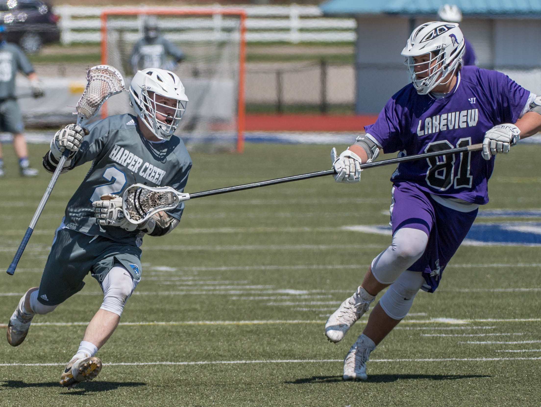 Harper Creek's Connor Gilbert (24) advances the ball against Lakeview's Austin Gayda (81) in the All City Lacrosse Tournament on Saturday.