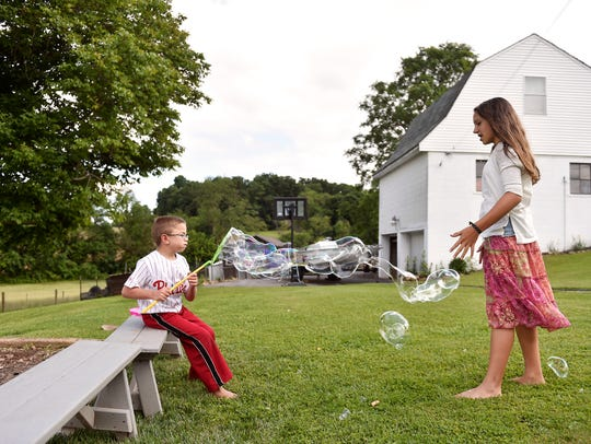 Sean Kisielnicki, 7, blows soap bubbles toward sister