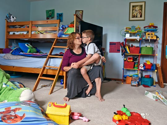 Trish Kisielnicki holds her son Sean, 7, in her lap
