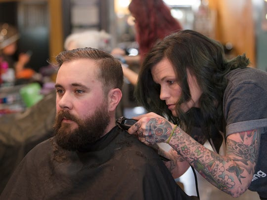 Jen Powell , Seville Salon manager, gives a haircut to Damon Delmont on Thursday, Jan. 18, 2018, at Seville Salon in Montgomery, Ala.