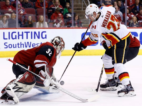 Arizona Coyotes goaltender Antti Raanta (32) makes a save on a shot by Calgary Flames center Sean Monahan (23) during the first period of an NHL hockey game Monday, March 19, 2018, in Glendale, Ariz. (AP Photo/Ross D. Franklin)