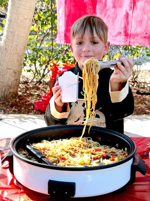 Turtle River Montessori second-grader Frankie Flora serves Chinese Lo Mein and vegetables to classmates while wearing traditional Chinese Changshan (tunic) at the school's Cultural Peace Festival on Feb.2.