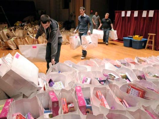 Henderson County JROTC students (L-R) Brandon Jones, David Basmadji, Kane Brooks and John Keeper carry gift bags to the stage at South Middle School Saturday morning as dozens of volunteers sort and fill gift bags with clothes and toys for about 600 needy children. This years Goodfellows fundraising campaign raised $33,000 to put on Sunday's Christmas party that will include a puppet show, a ventriloquist, clowns, face painting, cupcakes and ice cream, among other things. (Gleaner photo by Mike Lawrence ¥ 831-8346 or mlawrence@thegleaner.com) 11-19-2009