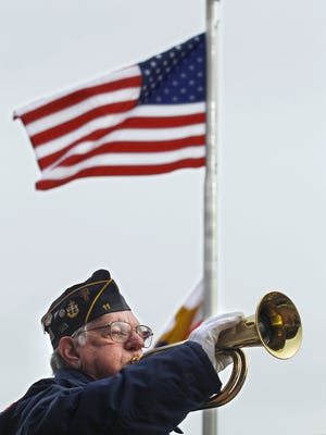 By John Terhune/Journal & Courier--Ralph Ward with the Sounding of Taps during Veterans Day Observance Friday, November 11, 2011, at Riehle Plaza in downtown Lafayette. Ward is a Navy veteran of WWII.