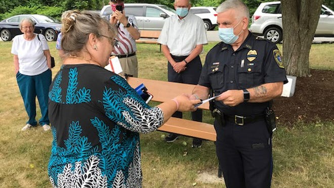 The Chocksett Club's Loret Schur (left) hands a check to Sterling Police Chief Gary Chamberland for the Police Association.
