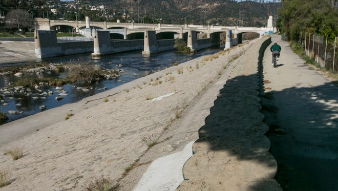 A cyclist rides along recently installed temporary flood control walls along the L.A. River in Los Angeles Friday, Feb. 12, 2016. Ten days with record heat and no rain have Californians worrying about the drought again.