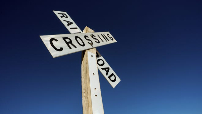 railroad crossing sign on blue sky