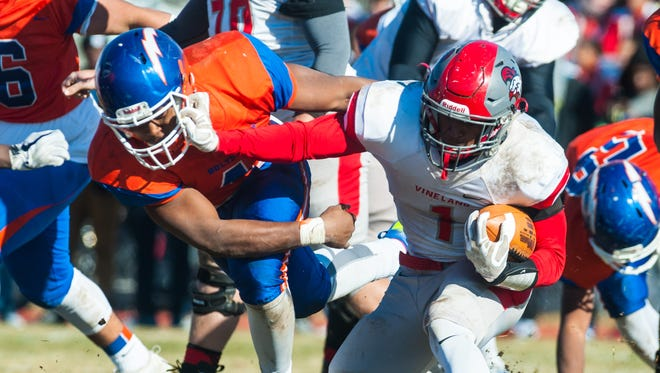 Vineland quarterback Isaih Pacheco (1) fights off a tackle against Millville at John Barbose Stadium on Thursday, November 23.