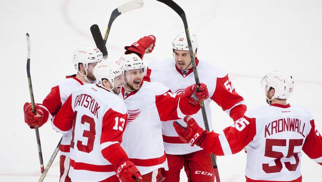 Detroit's Pavel Datsyuk, left, Tomas Tatar, and Jonathan Ericsson celebrate a goal by Datsyuk in the third period.            Detroit won 4-0 to take a 3-2 series lead.