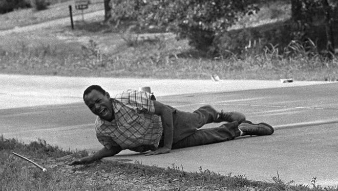 Civil rights activist James Meredith grimaces in pain as he pulls himself across Highway 51 after being shot in Hernando, Miss., on June 6, 1966. Meredith was leading the March Against Fear to encourage African Americans to exercise their voting rights when he was shot. He completed the march from Memphis, Tenn., to Jackson, Miss., after treatment of his wounds.