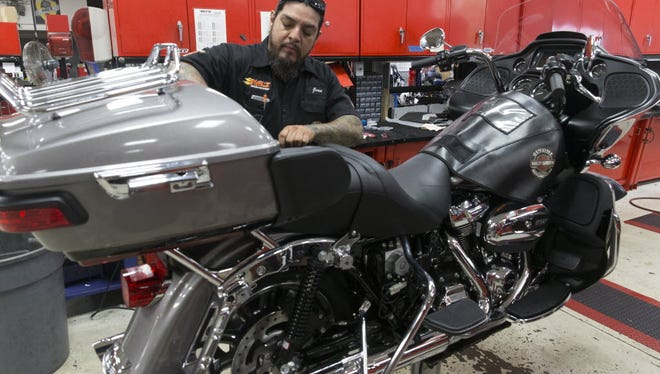 Jose Garza, a service technician at Hal's Harley-Davidson, prepares a bike for the Milwaukee Rally.