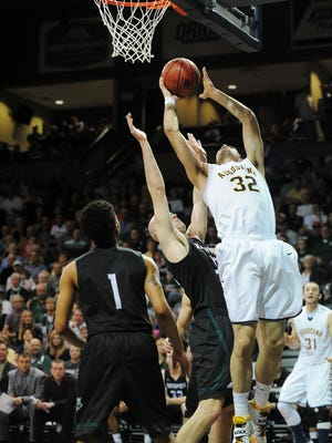 Augustana's Casey Schilling (32) goes up for a shot over Northwest Missouri State's Zach Schneider (33) and Justin Pitts (1) during a NCAA Division II MenÕs Central Region tournament semifinal game on Sunday, March 15, 2015, at the Sanford Pentagon in Sioux Falls, S.D.