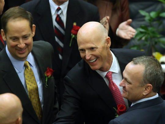 Gov. Rick Scott flanked by Sen. Joe Negron, R-Stuart,