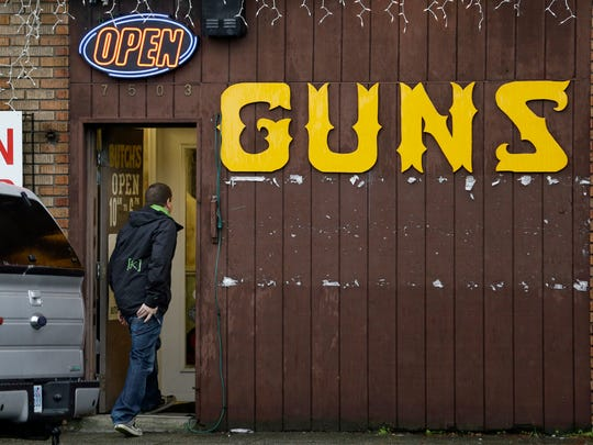 "A man walks into a gun shop in Seattle in 2012. The Washington Supreme Court upheld Seattle's so-called ""gun violence tax"" against a challenge from gun-rights groups Thursday Aug. 10, 2017. (AP Photo/Elaine Thompson,File)"