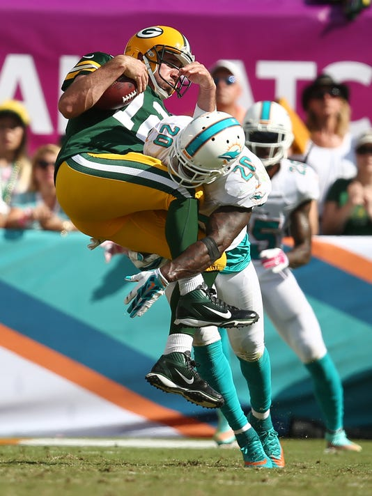Green Bay Packers quarterback Aaron Rodgers (12) is tackled by Miami Dolphins free safety Reshad Jones (20) during the second half of an NFL football game, Sunday, Oct. 12, 2014, in Miami Gardens, Fla. (AP Photo/J Pat Carter)