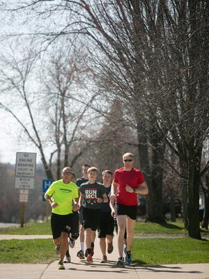 Jason Foemmel, front left, runs with the Marshfield High School's long distance runners from the track team along Becker Street in Marshfield on Thursday. Foemmel is an assistant track coach at Marshfield High School and will be running the Boston Marathon on Monday.